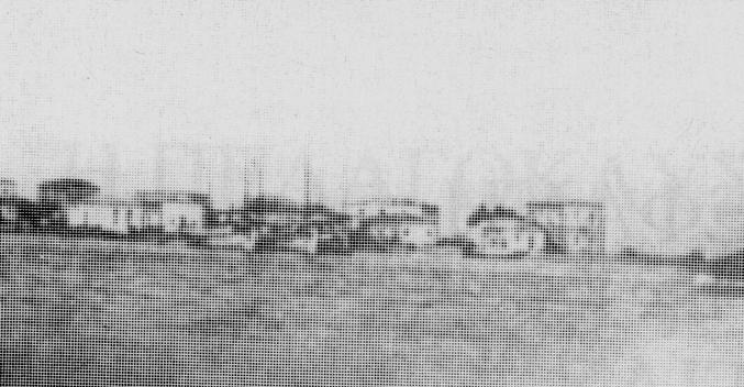 Η εικόνα της Ελαφονήσου μερικές δεκαετίες μετά την απελευθέρωσή της. Στην Β.Α. παραλία του οικισμού (στο σημερινό παλαιό λιμάνι ) διακρίνονται τα ιστιοφόρα και τα κωπήλατα πλεούμενα του νησιού. Τα άλμπουρα των μεγάλων καϊκιών ξεπερνούν κατά πολύ ακόμη και τα διώροφα παραλιακά σπίτια. (Φωτ. από το βιβλίο: Μέντης Κων/νος «Ελαφονήσι το Σμιγοπέλαγο Νησί», εκδόσεις Λαφονησιώτικη βιβλιοθήκη, Πειραιάς 1993)